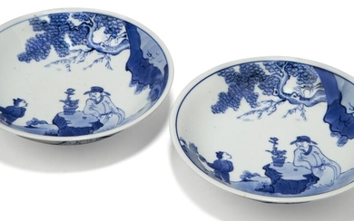 A pair of Chinese porcelain blue and white saucer dishes, Republic period, each painted with a scholar seated at a rock taking tea with an attendant, 17cm diameter