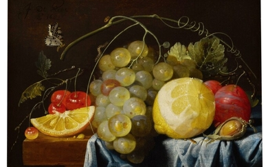 Still life of fruit, including lemons, grapes, pears and cherries, together with a hazelnut, all arranged on a table largely draped with a blue cloth