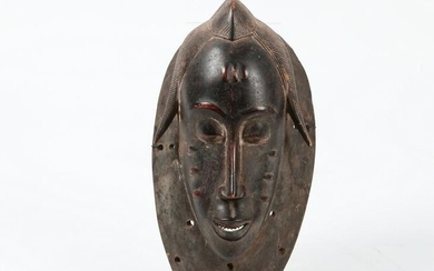 An African carved hardwood Guro mask, Ivory Coast