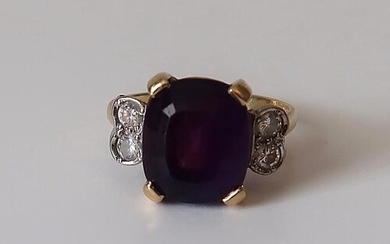 An amethyst dress ring flanked by a pair of circular diamond...