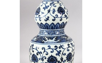 A CHINESE BLUE AND WHITE DOUBLE GOURD VASE, painted with lot...