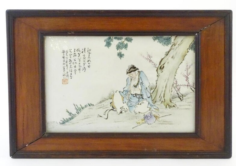 A Chinese porcelain plaque decorated with a seated