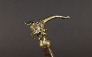 Cane with bronze knob featuring a character's head with pointed cap. Traces of silver plating. Height 86,5 cm