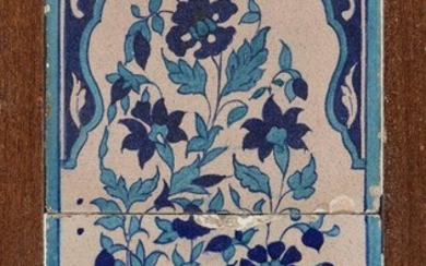 A Multan pottery tile panel with floral decoration, North India, early 19th century, formed of two tiles decorated in turquoise and cobalt and depicting a floral spray within a cusped arch, set in a wood frame, 52 x 30cm.