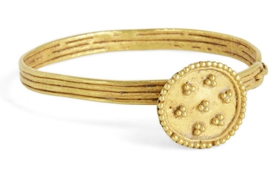 A gold bangle for a baby, Iran, 12-13th century, the band formed of four, wires soldered together, the raised bezel with disc face set with seven clusters of gold granules, hinge to one side, 4cm. diam.