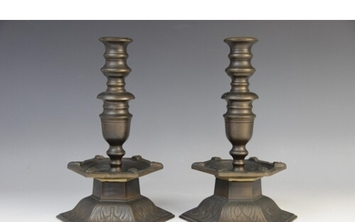 A pair of Arts and Crafts style bronze candlesticks, the hex...