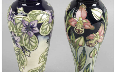 A Moorcroft pottery vase, decorated in a trial pattern of pink flowers, together with another similar example, decorated with lilac flowers. (2).