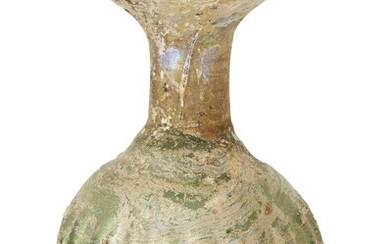A Roman glass sprinkler flask, circa 4th century A.D., the globular body with vertical ribbing, the cylindrical neck constricted on the insde at the base of the neck, with broad everted rim, 8cm. high Provenance: Purchased in 1983 from George...