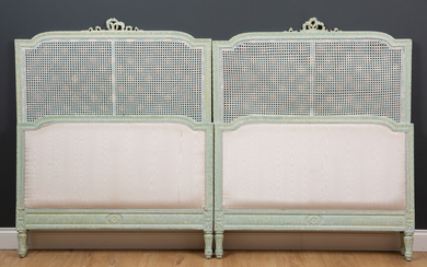 A pair of green painted single beds