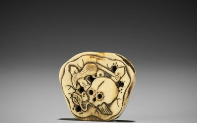 A STAG ANTLER NETSUKE WITH SKULL AND LOTUS