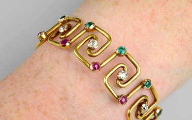 An early 20th century 18ct gold emerald, diamond and ruby bangle.