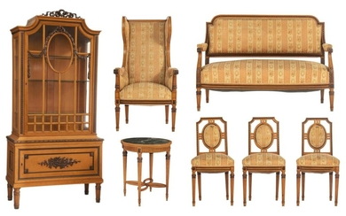 A Louis XVI style furniture set, containing a display cabinet, a round centre table, wall mirror, a wing armchair, and three chairs