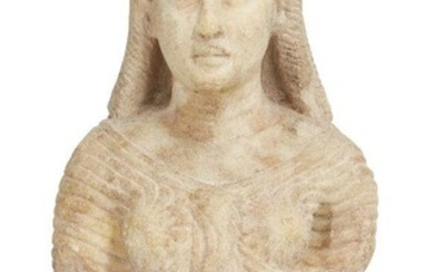 A Roman marble bust of Isis, circa 1st Century A.D., the wavy hair with central parting, falling in eight tight ringlets below the fillet, her face with large almond-shaped eyes and full lips, wearing a finely pleated close-fitting robe typically...