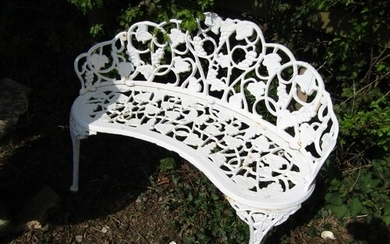 A cast iron garden bench of convex form with fruiting vine d...