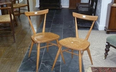 A pair of mid 20thC light elm and beech Ercol Stacking Chair...