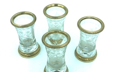 A set of four rock crystal and gilt metal shot glasses. The ...