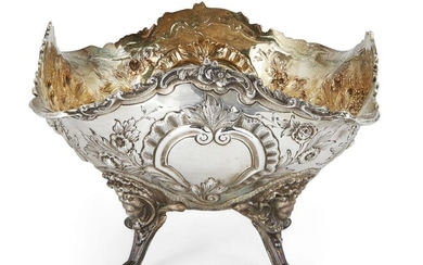 A Victorian silver fruit bowl with gilded interior, London, c.1899, Goldsmiths & Silversmiths Co., of shaped square form, the sides repousse decorated with baskets of flowers and fruit, vacant cartouches to two sides, the dish raised on four legs...