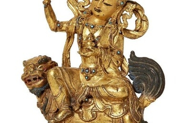 Property of a Gentleman (lots 36-85) A Sino-Tibetan gilt-bronze figure of Green Tara on a Buddhist lion, 18th/19th century, Tara cast seated in lalitasana wearing a five-peaked crown set with turquoise cabochons with her right hand held aloft...