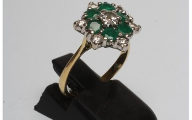 A DIAMOND AND EMERALD CLUSTER RING, the central diamond of a...