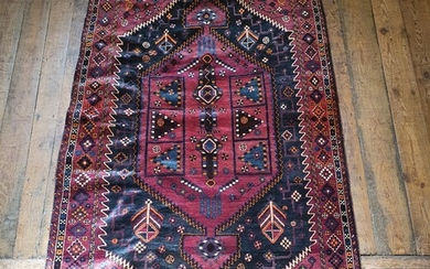 A Persian red ground rug, with multiple borders, centre with...
