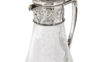 A Victorian silver mounted glass ewer, Sheffield, c.1875, W & G Sissons, the body etched with ivy swag clusters and raised on a circular cut glass foot, the angular foliate design handle to silver collar richly decorated with floral and foliate...