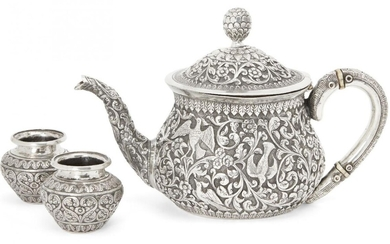 A silver repousse Kutch teapot, India, circa 1860 and two silver spice containers, of squat form with curved handle and spout, hinged domed lid with pinecone finial, the teapot handle with heat insulating discs of ivory, finely decorated to body...