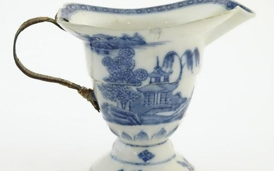 A helmet jug with blue and white decoration with a