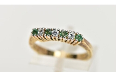 A GOLD-PLATED EMERALD AND CUBIC ZIRCONIA HALF ETERNITY RING,...
