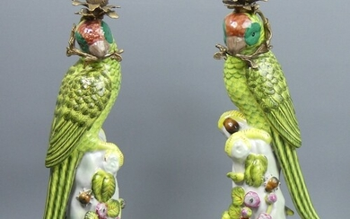 A pair of bronze and porcelain parrot design large candlesti...