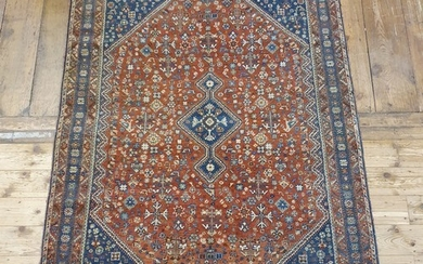 A Persian red ground carpet, multiple borders, centre with r...