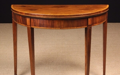 A Georgian Inlaid Mahogany Card Table. The hinged fold-over demi-lune top inlaid with cross-banded borders...