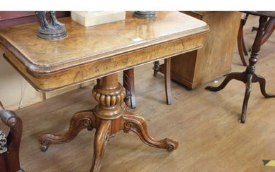 A Victorian walnut fold over top card table, on carved colum...