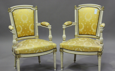 A pair of 20th century Louis XVI style white painted and gilt fauteuil armchairs, upholstered in pat