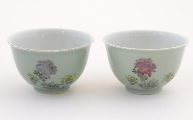 A pair of Chinese tea bowls decorated with flowers and