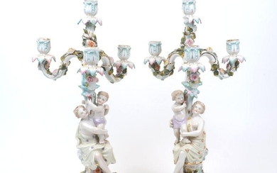 A pair of Sitzendorf three branch figural candelabras, 19th Century, of cream ground and turquoise and pink colour ways, the branches with floral encrustations and leaf sconces atop stems modelled as a draped classical nude supporting a putto, to a...