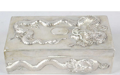 A Chinese export silver table cigarette box decorated with dragons in relief.