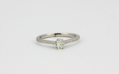 A Jenny Packham 18ct white gold oval cut diamond set solitaire ring with diamond set shoulders, approx. 0.33ct, (M.5).
