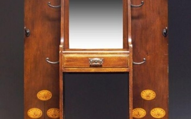 An Edwardian mahogany and marquetry inlaid hall stand, the back panel with hanging rail and mounted with hooks about a central rectangular mirror above single drawer and stick/umbrella stand and flanked by Art Nouveau floral marquetry, on bracket...