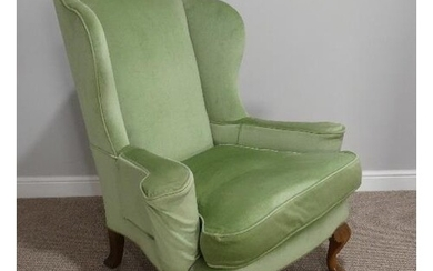 An early 20thC Wing Armchair, in green upholstery, with carv...