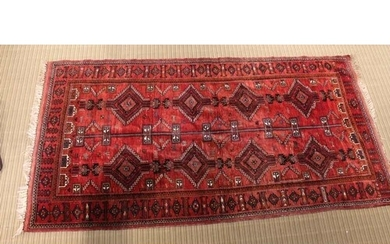 A MIDDLE EASTERN WOVEN WOOLLEN PIGEON RED GROUND FLOOR CARPE...