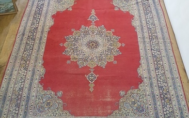 A Persian red ground carpet with multiple borders, centre wi...