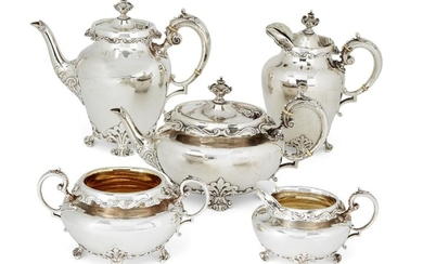 A five-piece Victorian silver tea service, London, c.1899, Goldsmiths & Silversmiths Company (hot water pot c.1900), of oval form, the body of each raised on four scroll feet to foliate shoulders, the shaped rims decorated with repeating c-scroll...