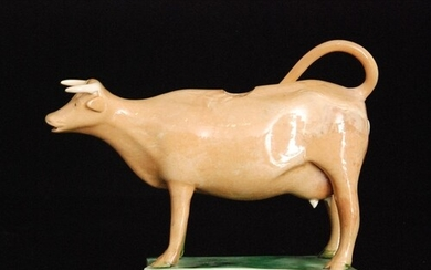 An early 19th Century Staffordshire cow creamer, cow decorat...