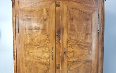 A walnut and walnut veneer cupboard opening with two doors,...