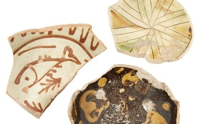 Three large Byzantine glazed pottery fragments, 10th-13th century, the first with a fish in raised red on a cream ground, the second with radial design in ochre and green and the third with yellow splashes on a dark brown ground, largest 15cm...