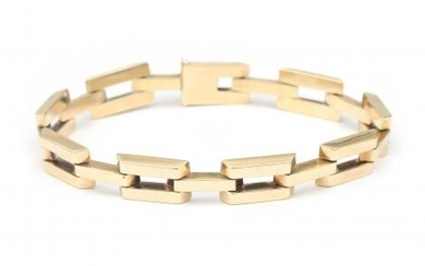 A 14 karat gold fifties bracelet. Composed of rectangular links with feceted edges to a tongue clasp with safety eye. Gross weight: 22.3 g.