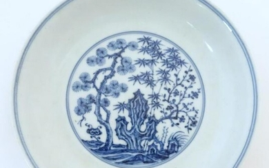 A Chinese blue and white dish with blossoming trees and