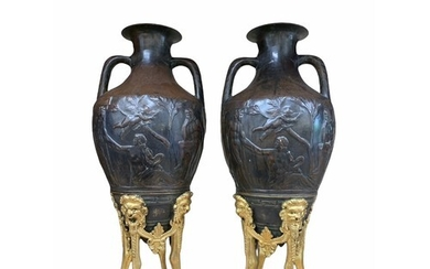 A PAIR OF 19TH CENTURY BRONZE AND PARCEL GILT URNS Cast wit...