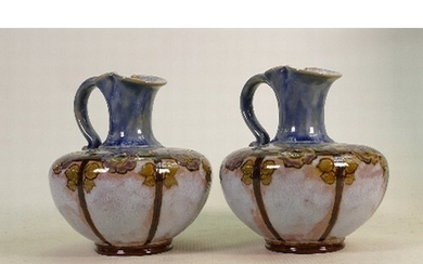 A Pair of Doulton Lambeth ewers: Decorated with stylised flo...