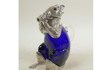 A silver plated and blue glass claret jug in the form of a s...